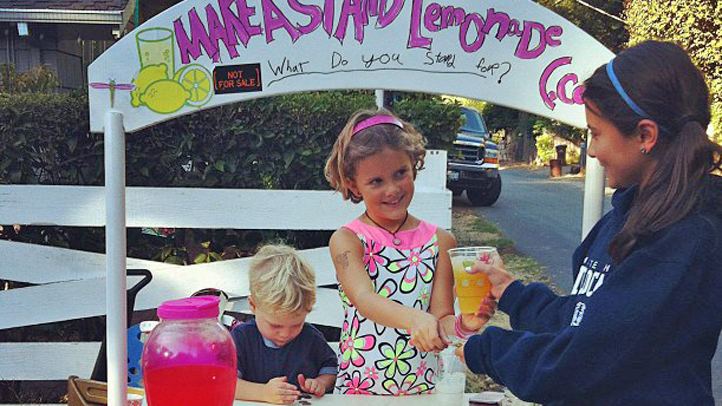 Vivienne Harr (center) and her brother, Turner, (left) sell lemonade to a customer in 2012. Now, Make A Stand Lemon-aid is available in bottles at 70 locations on the West Coast.
