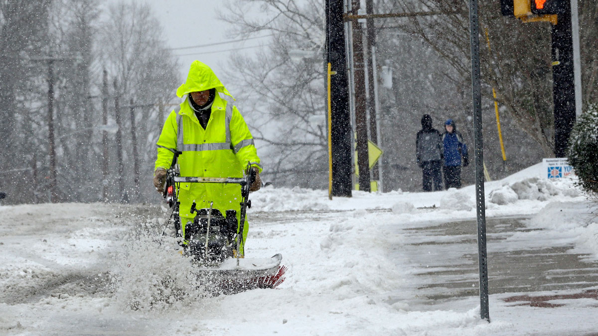 A city worker removes snow from a crosswalk as a winter storm blankets the area in Carrboro, N.C., Saturday, Jan. 7, 2017.